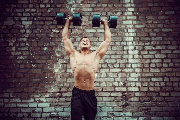 Cara musculoso fazendo exercícios com halteres contra uma parede de tijolos