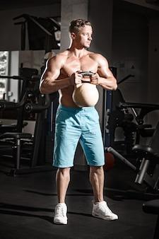 Cara musculoso fisiculturista fazendo exercícios com peso no ginásio