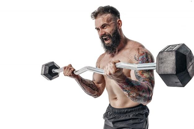 Cara musculoso fisiculturista fazendo exercícios com pesos