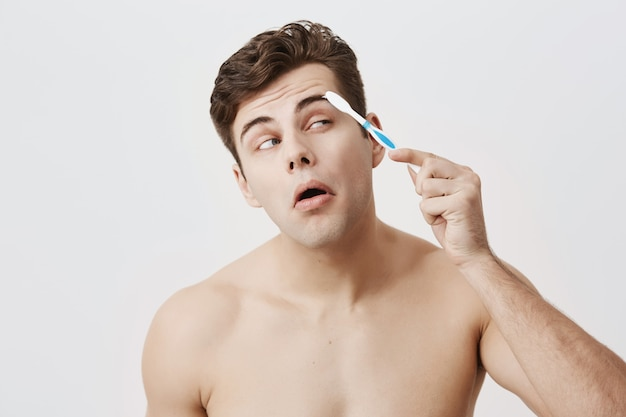 Cara musculoso nu positivo com penteado na moda, pele saudável, fazendo caretas, concentrado em pentear as sobrancelhas com escova de dentes. levantamento masculino bonito atrativo.
