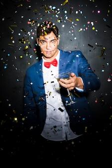 Cara na jaqueta de noite com vidro entre confetes jogando