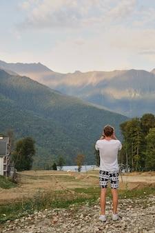 Cara nas montanhas tirando fotos do pôr do sol