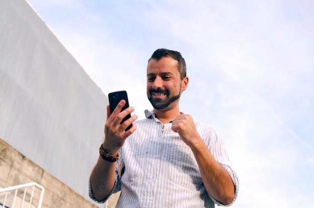 Cara, olhando para o celular, feliz lendo boas notícias. homem recebe resposta positiva em inteligente pho