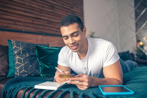 Cara olhando para um cartão de visita fazendo anotações em um caderno, deitada em uma cama, sorrindo.