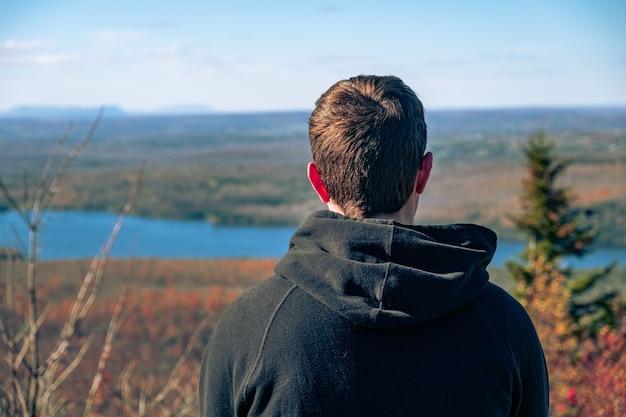 Cara, olhando para uma bela paisagem de rio em um dia ensolarado