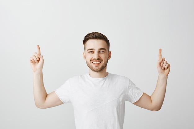 Cara orgulhoso feliz sorrindo e apontando o dedo para cima