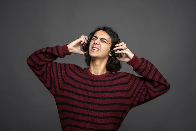 Cara ouve música no fone de ouvido