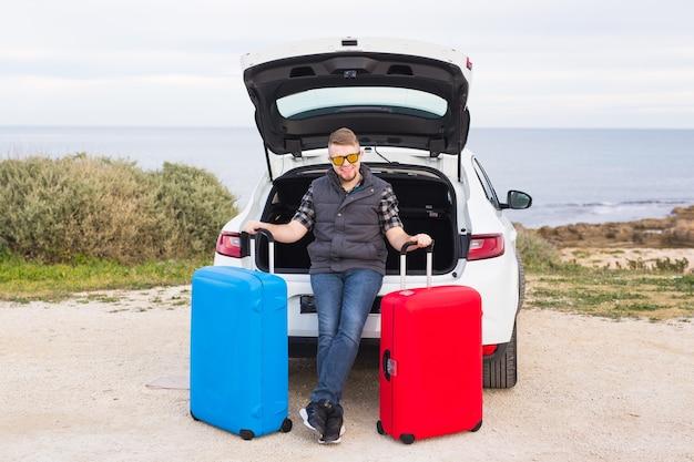 Cara parado atrás do carro sorrindo e se preparando para ir. jovem rindo em pé perto do porta-malas aberto de um carro.