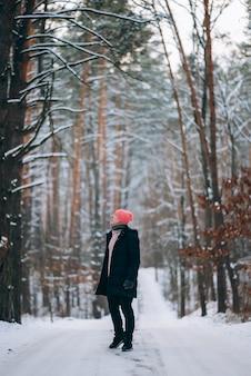 Cara parado na estrada, no meio da floresta, cercado de neve