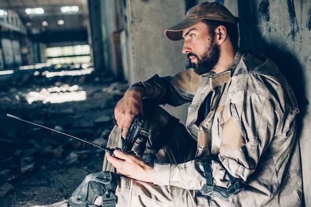 Cara pensativa de uniforme está sentado no chão e inclinando-se para a parede. ele está olhando para a frente. warrior está cansado. homem está segurando o cara preto e rádio portátil nas mãos