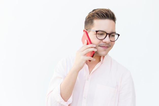 Cara pensativa em óculos falando no celular e desviar o olhar