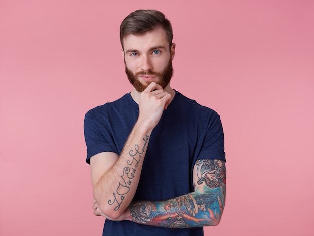 Cara pensativo e atraente de barba vermelha com olhos azuis, vestindo uma camiseta azul, segura a mão no queixo e olha pensativo para a câmera isolada sobre fundo rosa.