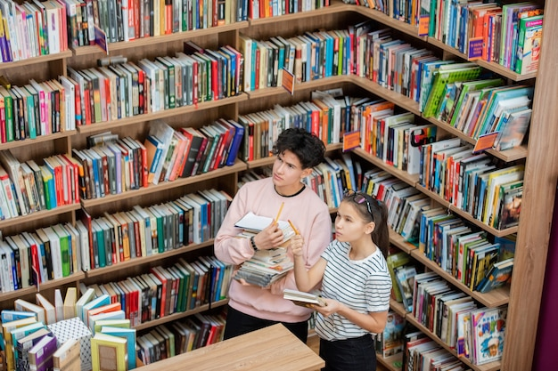 Cara pensativo e seu colega inteligente olhando para uma grande estante de livros na biblioteca da faculdade enquanto a garota apontando para um dos livros