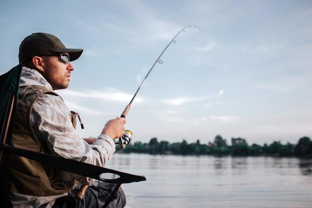 Cara pensativo está sentado na beira da água e olhando para a direita. ele segura a vara nas mãos. é tarde e frio lá fora.