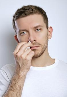 Cara pingando gotas nasais no nariz, retrato, close-up