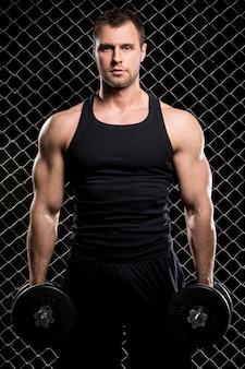 Cara poderoso com um halteres mostrando os músculos na cerca