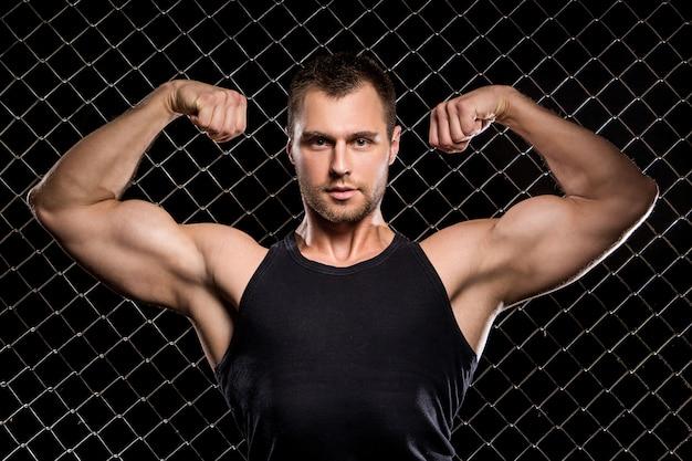 Cara poderoso, mostrando seus músculos na cerca