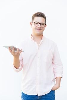 Cara positiva de óculos, segurando o tablet e olhando