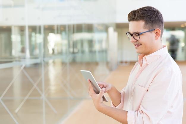 Cara positivo em copos usando tablet no corredor do escritório ou hotel