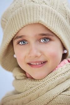 Cara preciosa de uma menina adorável sobre fundo azul