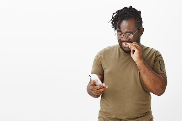 Cara preocupado de óculos posando contra a parede branca com seu telefone