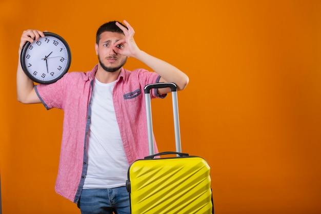 Cara preocupado jovem viajante bonito segurando o relógio em pé com mala fazendo sinal ok e olhando através deste sinal com expressão triste no rosto sobre fundo laranja