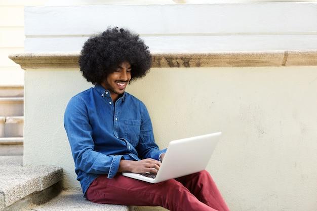Cara preta legal usando laptop fora