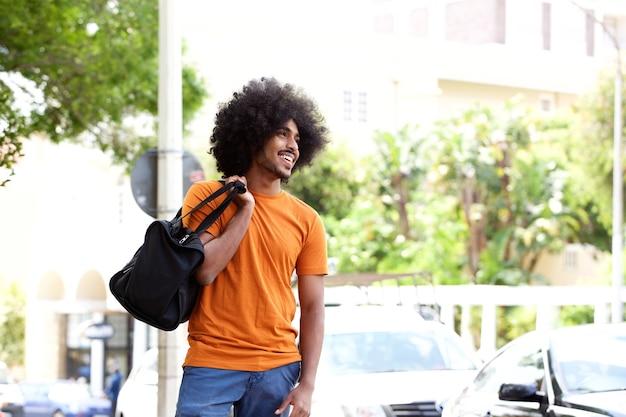 Cara preta sorridente carregando mala de viagem