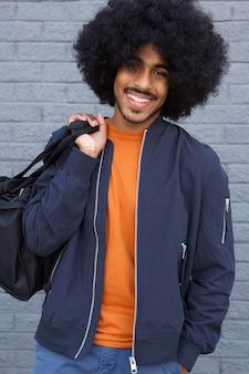 Cara preta sorridente com saco de exploração afro