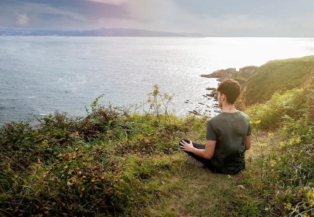 Cara relaxado sentado na grama meditando