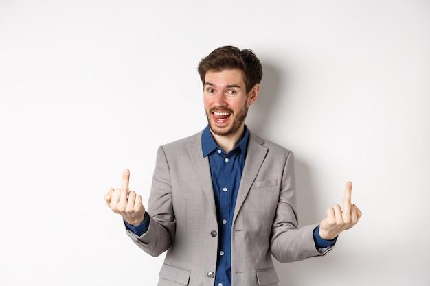 Cara rude e ignorante em um terno de negócio mostrando os dedos médios e a língua, sorrindo enquanto zomba das pessoas, foda-se o seu gesto, de pé sobre um fundo branco.