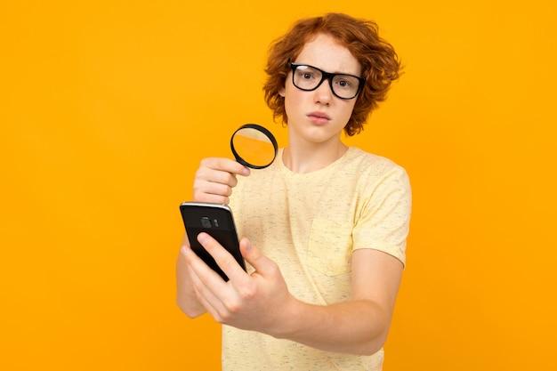 Cara ruiva em uma camiseta olha para um smartphone através de uma lupa em um amarelo