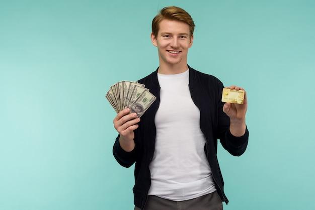 Cara ruivo desportivo alegre mostra dinheiro e cartão de crédito em um fundo azul.