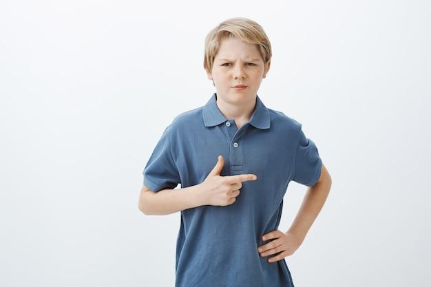 Cara se sentindo inseguro sobre o garoto da porta ao lado. retrato de criança suspeita e duvidosa com cabelo loiro, segurando a mão no quadril, franzindo a testa e apontando para a direita com o indicador
