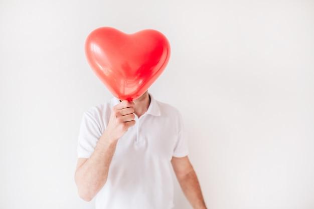 Cara segura balão vermelho em forma de coração na frente. cubra ou oculte. ame.