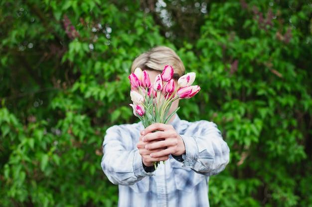 Cara segura um buquê de tulipas segurando-as na frente dele