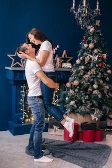 Cara segurando a garota nos braços e sorrir perto da lareira e da árvore de natal. perfil.