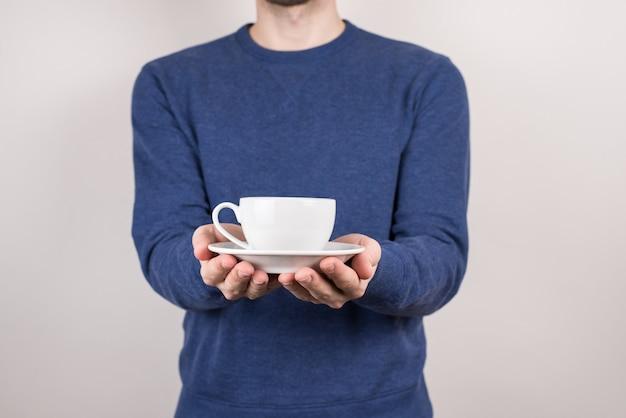 Cara segurando a xícara em fundo cinza isolado de pires