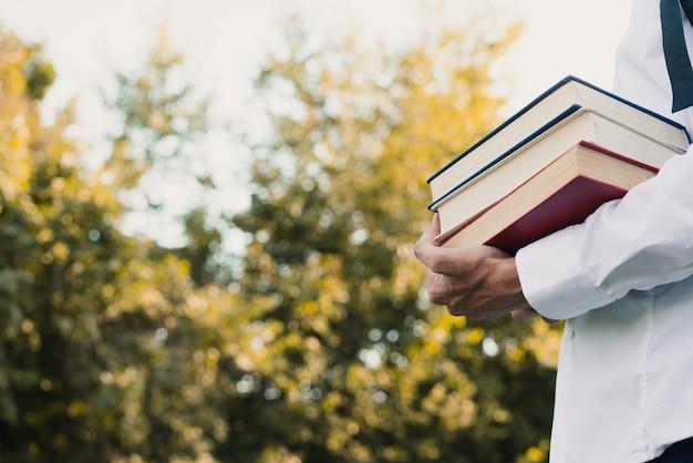 Cara segurando livros na mão