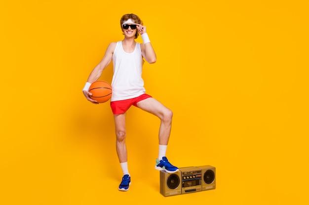 Cara segurando na mão um boombox de passo de bola laranja