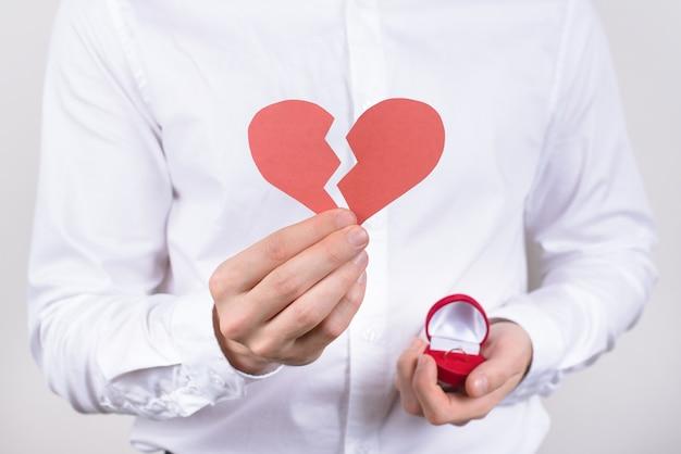 Cara segurando um coração de papel quebrado e uma caixa de anel