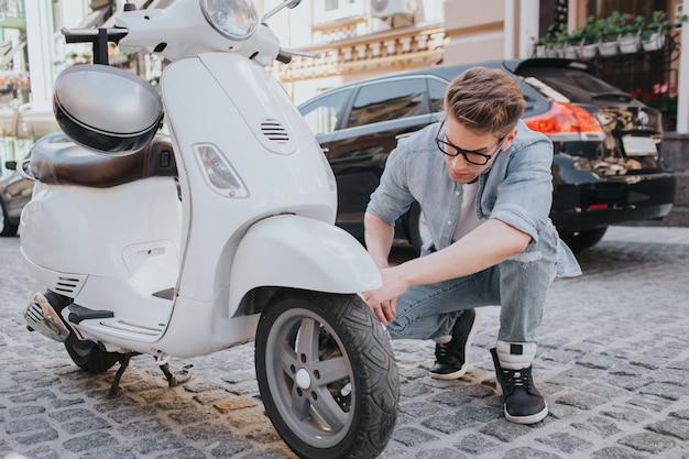 Cara sentado em posição agachada e olhando para a roda da motocicleta