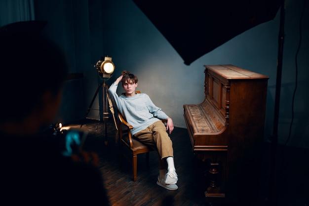 Cara sentado em uma cadeira ao lado do piano posando de foto