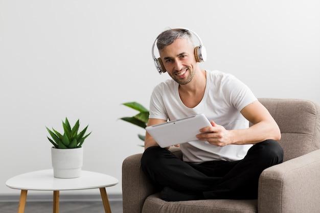 Cara sentado em uma cadeira e segurando um tablet digital
