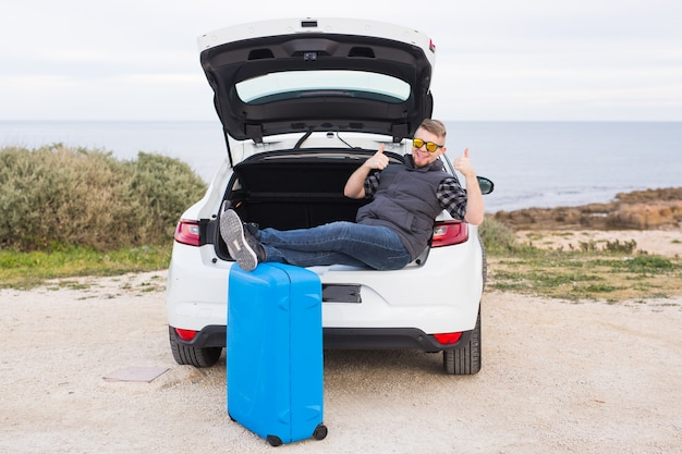 Cara sentado na parte de trás do carro, sorrindo e mostrando os polegares. jovem rindo sentado no porta-malas aberto de um carro.