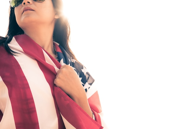Cara séria da mulher coberta pela bandeira dos eua, conceito do dia da independência dos eua.
