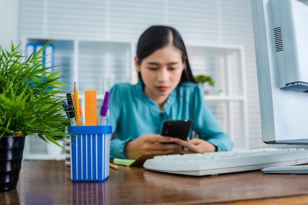 Cara séria, olhando para a tela do telefone móvel esperto. mulher asiática nova que trabalha em casa após a pandemia do coronavírus (covid-19) no mundo.