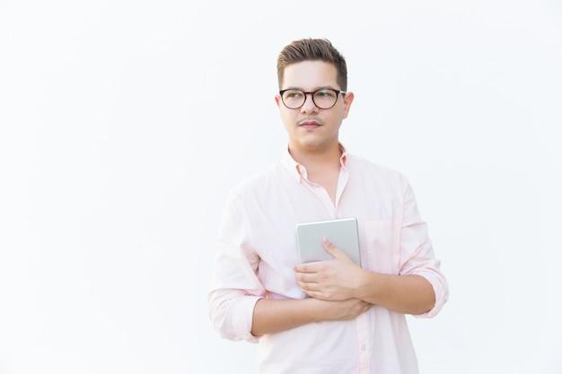 Cara séria pensativa em óculos abraçando tablet