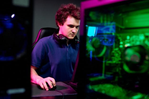 Cara sério com fones de ouvido no pescoço e olhando para a tela do computador durante um jogo cibernético de e-sport enquanto joga em um clube contemporâneo