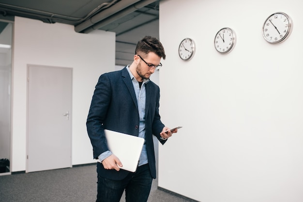 Cara sério de óculos está andando no escritório. ele veste camisa azul, jaqueta escura, jeans e barba. ele está digitando no telefone e segura o laptop na mão.